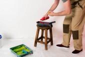 Fotografie Oříznout záběr člověka v práci celkové nalití barvy z láhve do váleček zásobník na židli