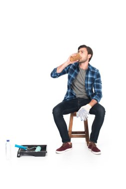 man resting on chair and drinking coffee near roller tray and paint roller isolated on white background