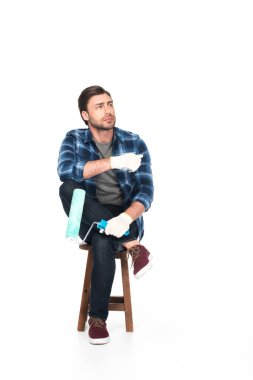 man in protective gloves sitting on chair with paint roller isolated on white background