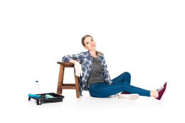 woman sitting on floor near chair, roller tray, paint roller and bottle isolated on white background