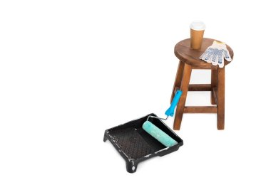 closeup shot of chair, coffee cup, protective gloves, roller tray and paint roller isolated on white background