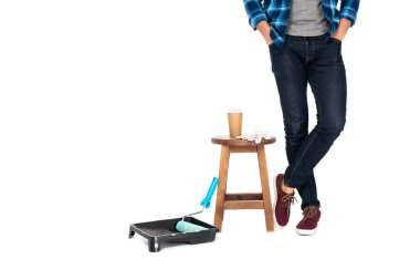 cropped shot of man standing near chair with protective gloves, coffee cup and roller tray with paint roller isolated on white background
