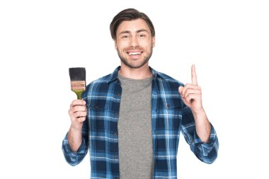 smiling man holding paint brush and doing idea gesture isolated on white background
