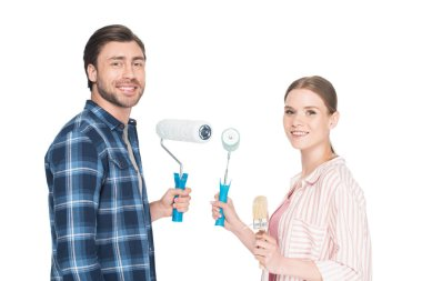 smiling young couple with paint rollers and paint brush isolated on white background