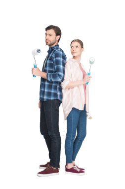 couple with paint rollers standing back to back isolated on white background