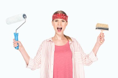 screaming woman in headband holding paint roller and paint brush isolated on white background