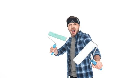 angry young man in headband holding paint rollers isolated on white background