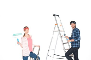 boyfriend and girlfriend on ladders with paint rollers isolated on white background