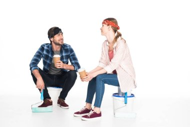 smiling young couple sitting on paint tins with paint rollers and drinking coffee from paper cups isolated on white background