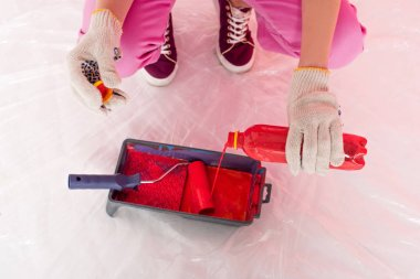 cropped shot of woman in protective gloves pouring red paint from bottle into roller tray with paint roller
