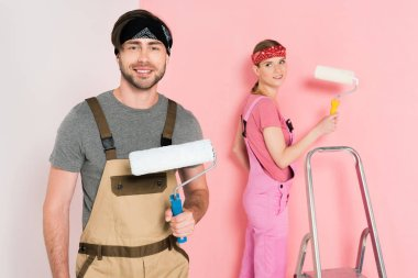 smiling man with paint roller and his girlfriend standing behind and painting wall
