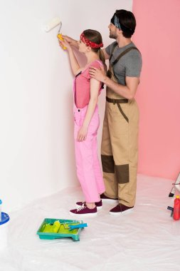 young man in working overall teaching girlfriend painting wall by paint roller