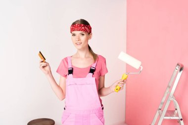 young woman in headband and working overall holding credit card and paint roller