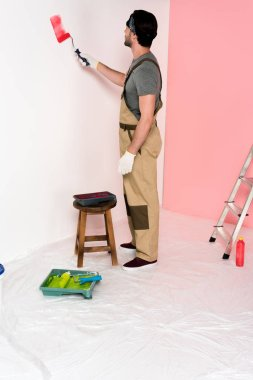 young man in working overall and headband painting wall in red by paint roller near chair with roller tray