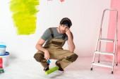 Fotografie Müder junger Mann sitzt mit Farbroller neben Leiter vor bemalter Wand