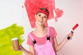 Lächelnde Frau mit gemaltem Gesicht, die eine Tasse Kaffee und eine Farbwalze in der Hand hält