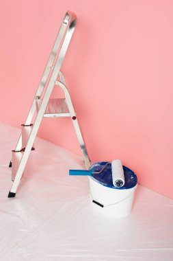 close up view of paint roller on paint tin and ladder in front of painted wall