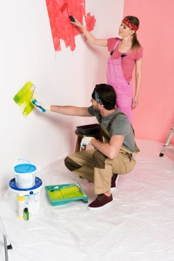 young couple in working overalls painting wall by paint rollers
