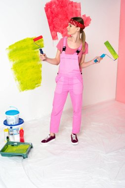 front view of woman in headband and working overall holding paint rollers standing near roller tray, paint tins and bottles