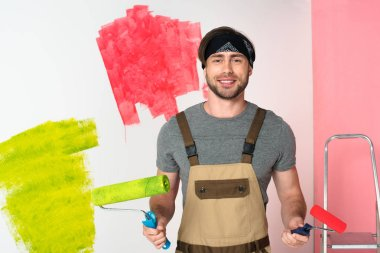 young smiling man in working overall with paint rollers in front of painted wall