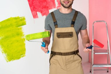 cropped image of man in working overall with paint rollers near ladder