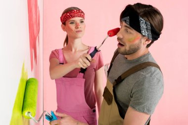 young woman in working overall painting face of shocked boyfriend by paint roller