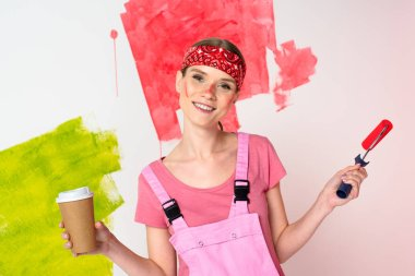 smiling woman with painted face holding paper cup of coffee and paint roller