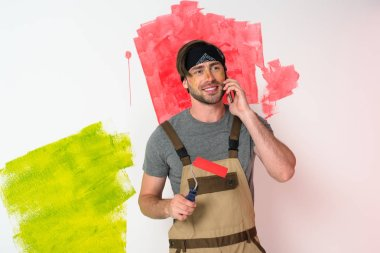 young man in headband talking on smartphone and holding paint roller in front of painted wall