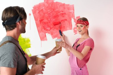 young man giving paper cup of coffee to smiling girlfriend while she painting wall