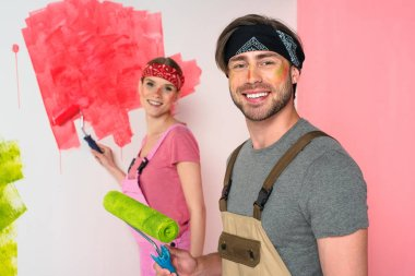 smiling young couple in working overalls with painted faces holding paint rollers