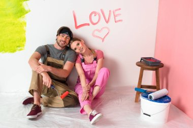 young couple in working overalls sitting near wall with lettering love and heart symbol