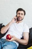 usmívající se muž mluví na smartphone a drží jablko v ruce doma