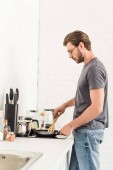 Fotografie side view of young man cooking on stove with frying pan and spatula at kitchen