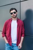 elegáns, fiatal férfi-modellt a napszemüveg, fekete fal közelében pózol