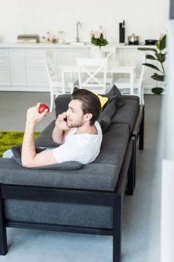 side view of man talking on smartphone and sitting on couch with apple in hand at home
