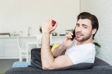smiling man talking on smartphone and sitting on couch with apple in hand at home