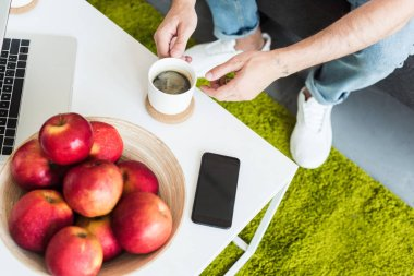 partial view of man taking coffee cup from table with smartphone, laptop and apples at home