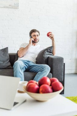 man talking on smartphone and sitting on couch with apple in hand at home