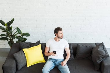 high angle view of young man sitting on sofa with smartphone in hand at home
