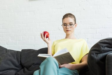 young attractive woman in eyeglasses reading book and holding apple on sofa at home