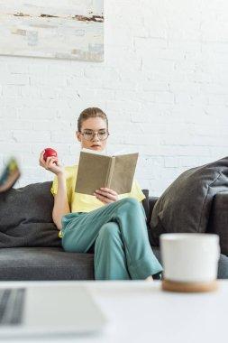 young attractive woman in eyeglasses holding apple and reading book at home
