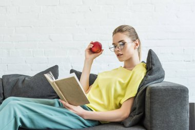 young woman in eyeglasses holding apple and reading book on sofa at home