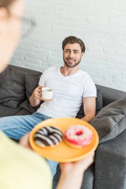 cropped shot of woman with donuts on plate and smiling boyfriend sitting on sofa with coffee cup at home