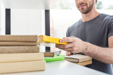 cropped shot of smiling man putting books on shelves at home