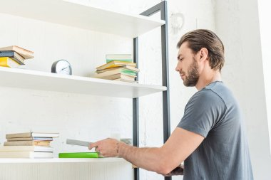 side view of young man putting books on shelves at home