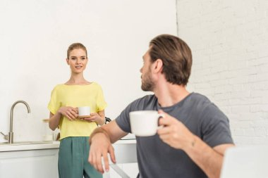young man with coffee cup sitting on chair and talking to girlfriend at kitchen