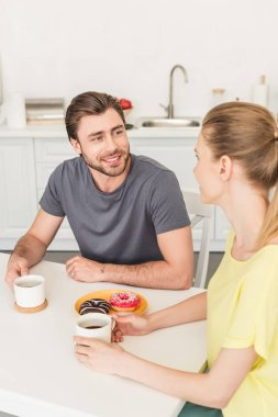 young smiling couple having conversation at kitchen table with donuts and coffee cups