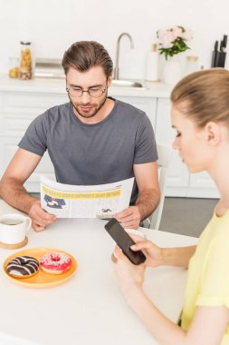 side view of woman using smartphone and boyfriend reading newspaper at table with coffee cups and donuts at kitchen