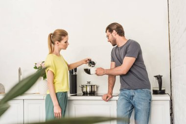 side view of woman pouring coffee to boyfriend at kitchen