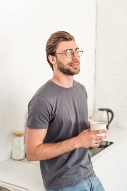 Smiling young man in eyeglasses drinking coffee at kitchen stock vector